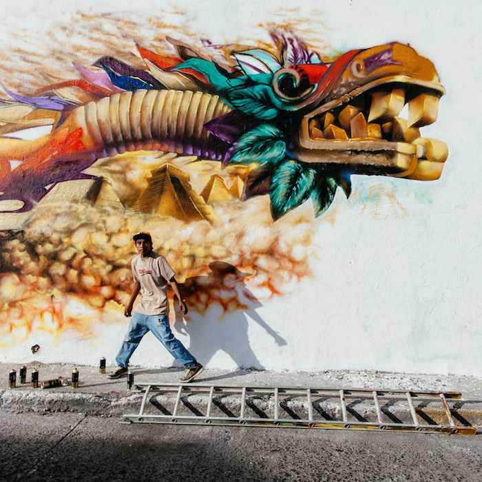 A grafitti artist works on a Quetzalcoatl, the benign prehispanic God that gave corn and fire to men.